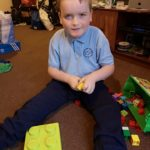Photo of boy with Smith-Kingsmore syndrome sitting on the floor
