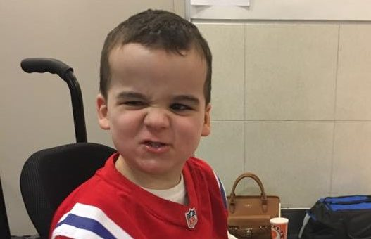 Photo of boy with Smith-Kingsmore syndrome with cute, tough look on face